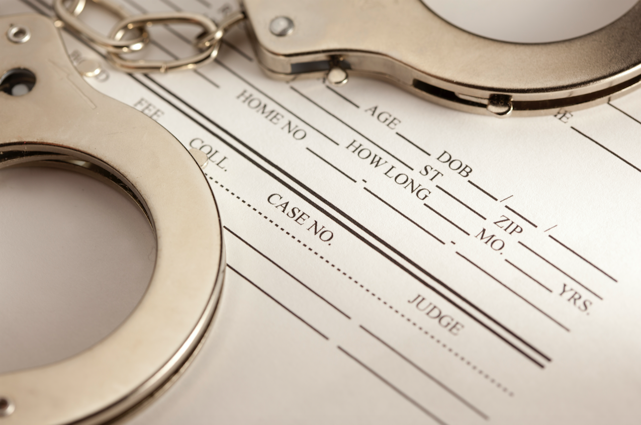 How to Get Your Criminal Record Expunged in Texas. Image of paperwork and handcuffs